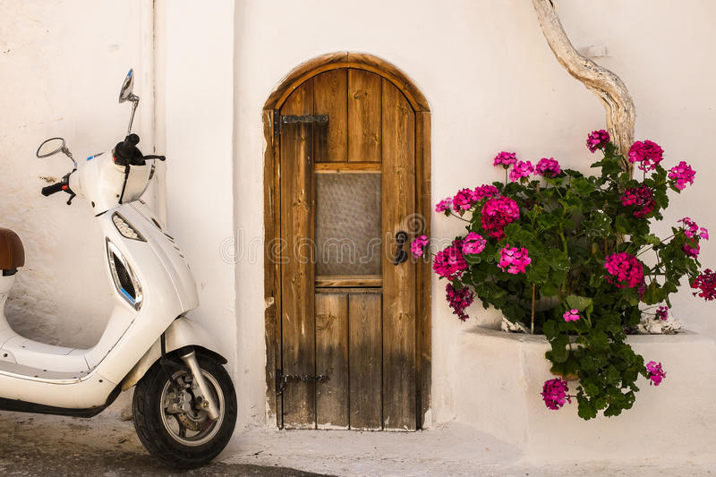 Village House in Crete, Greece. Exterior of a small village house with colourful flowers and a scooter parked outside. Kritsa, Crete, Greece royalty free stock images