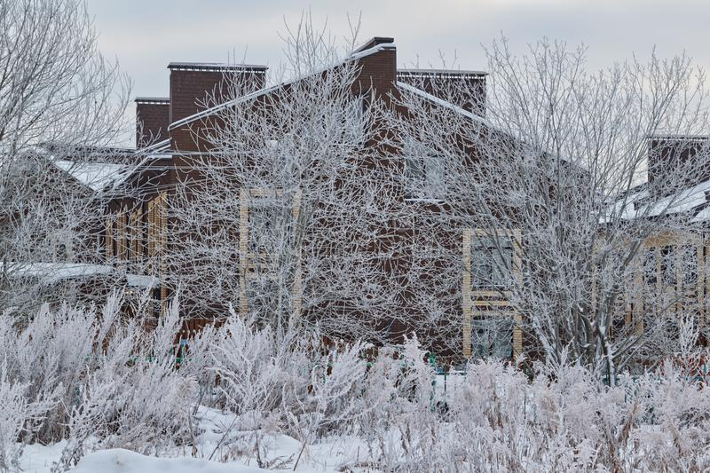 The village house is hidden by snow-covered branches of trees and bushes stock photos