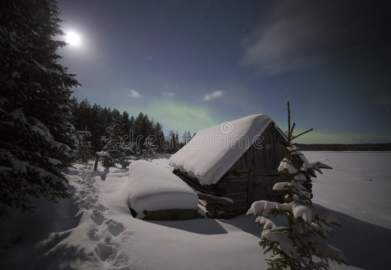 Village house in the lights of moon and Aurora borealis. stock images