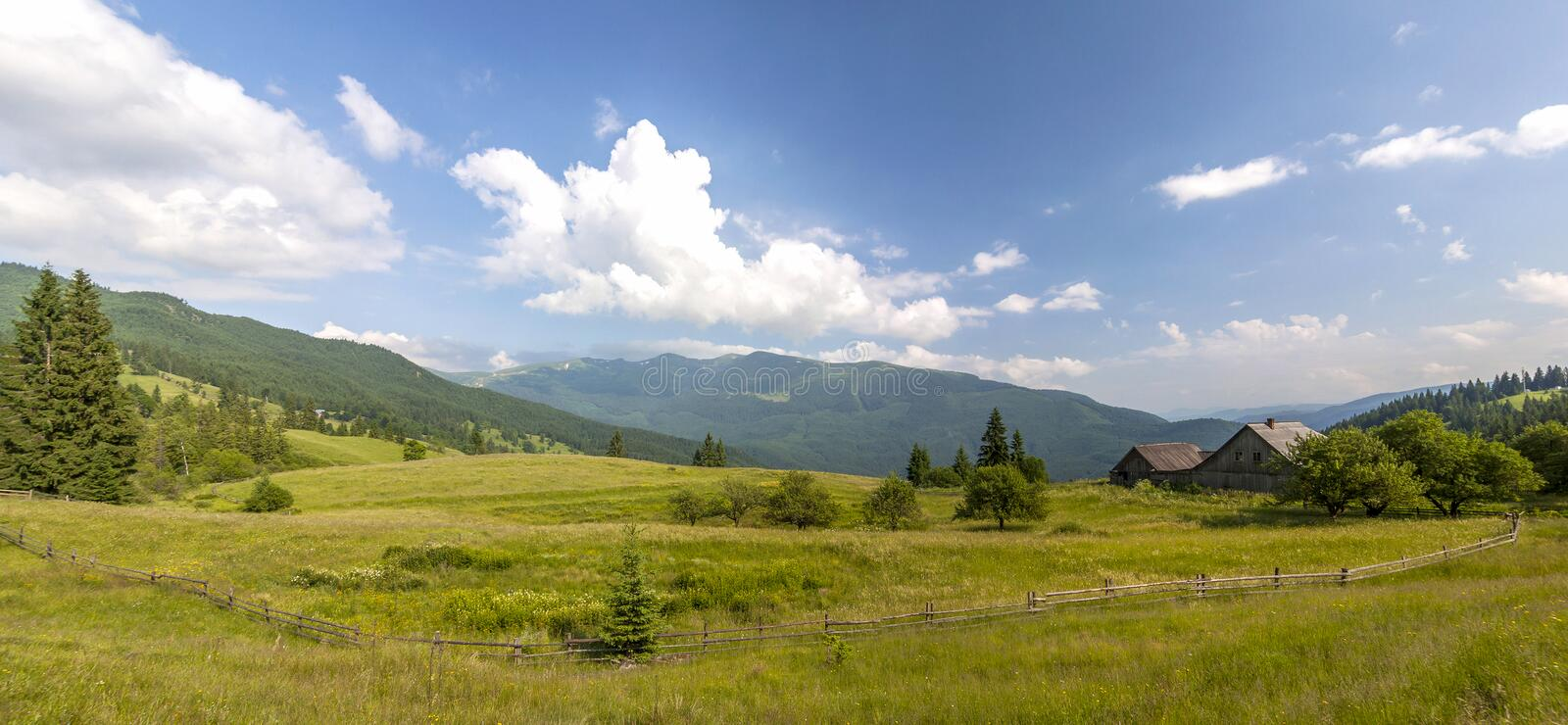 Village houses on hills with green meadows in summer day royalty free stock photo