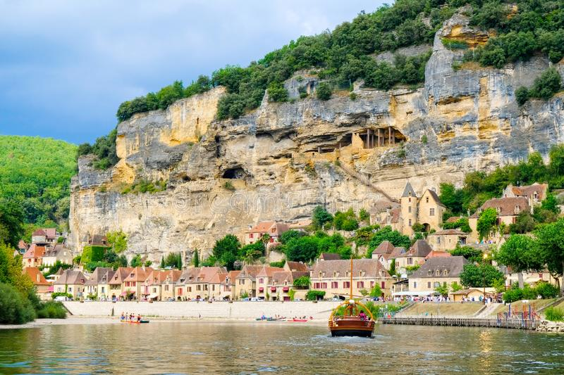 Village La Roque Gageac, France and embankment of the Dordogne River with gabare local boat stock afbeelding