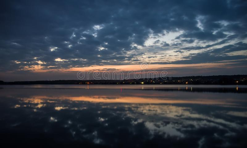 Village on the lake at sunset. Evening landscape with a reflection of the sky in the water. royalty free stock photo