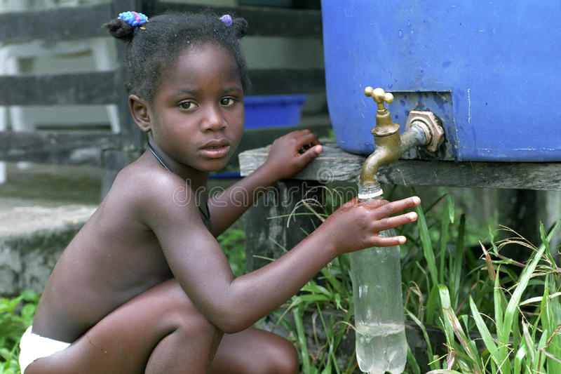 Village life, drain rainwater from rain barrel. Surinam, NDJUKA-girl from the Maroon villag Stoelmanseiland, which pulls water from a rain barrel. In the royalty free stock images