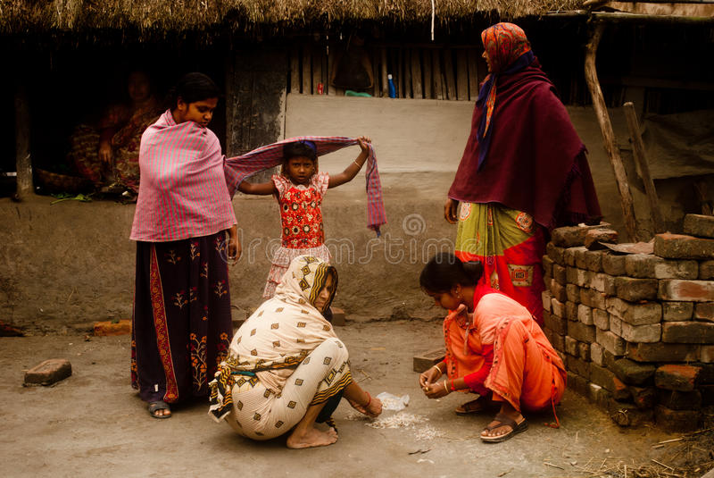 Village life of Sunderban, India. A group of village women is sharing a light moment with two other women during shaping small prawn in her kitchen at a village stock images