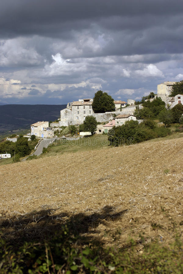 Village in the Luberon France. Moody sky, ploughed field. Village in the Luberon France. Under dark moody skies and a ploughed field in the foreground royalty free stock photo