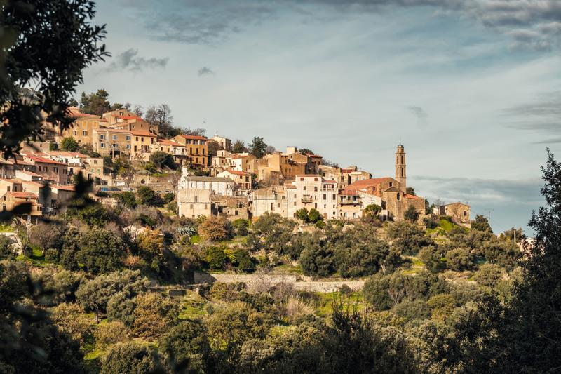 The village of Occhiatana in the Balagne region of Corsica. The ancient mountain village of Occhiatana lit by the morning sun and surrounded by autumnal trees in stock photography