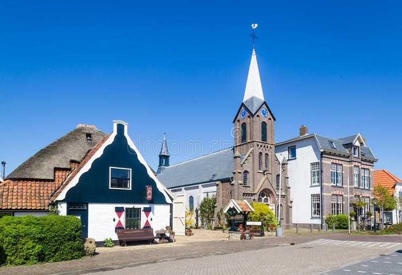 Village Oudeschild on Texel island in the Netherlands. Village Oudeschild with Martinus church and trraditional gable houses on the Wadden island Texel in the stock images