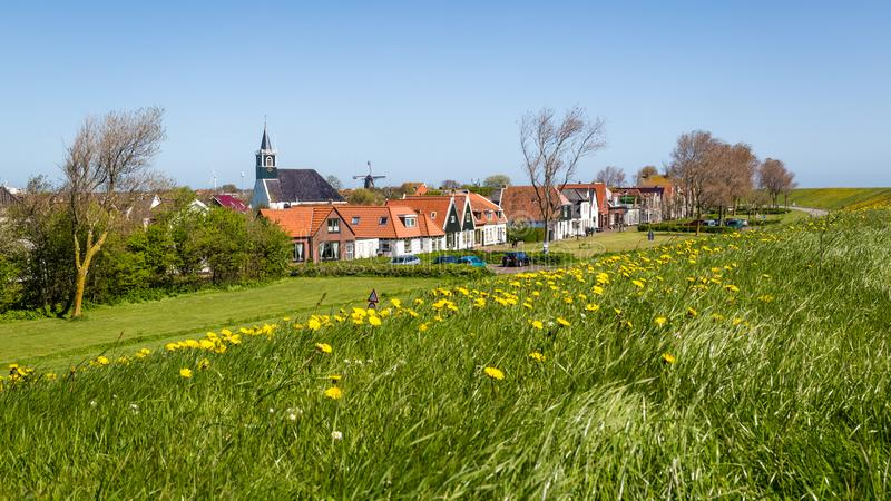 Village Oudeschild on Texel island in the Netherlands. Panorama Village Oudeschild with Martinus church, windmill and trraditional gable houses on the Wadden royalty free stock photography