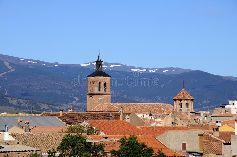 Village rooftops, La Calahorra, Spain. Village rooftops and church towers with the Sierra Nevada mountains to the rear, La Calahorra, Granada Province stock image