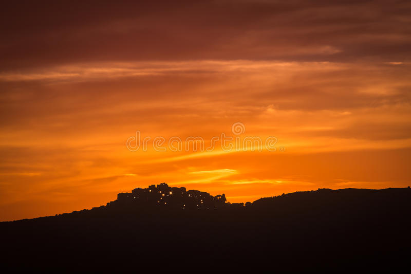 Village of Sant' Antonino in Corsica silhoutted against orange e stock photos