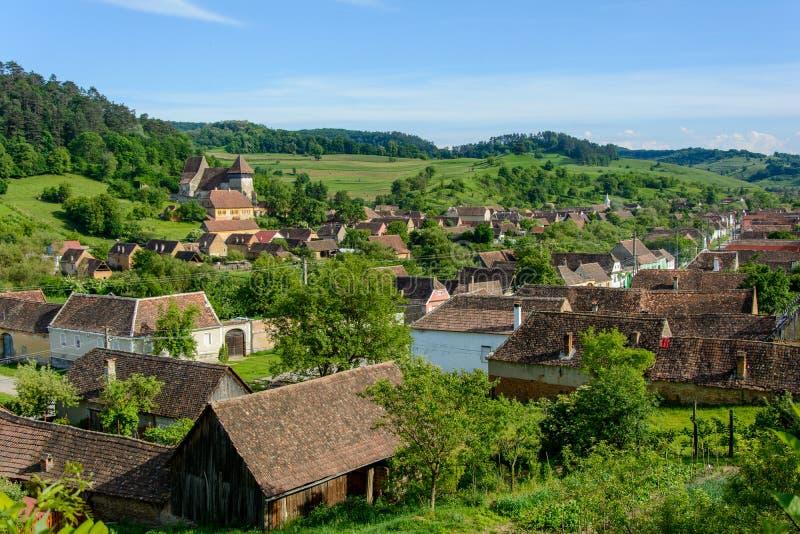 Village saxon de jument de Copsa avec son église enrichie, près de Biertan, le comté de Sibiu, la Transylvanie, Roumanie photos stock