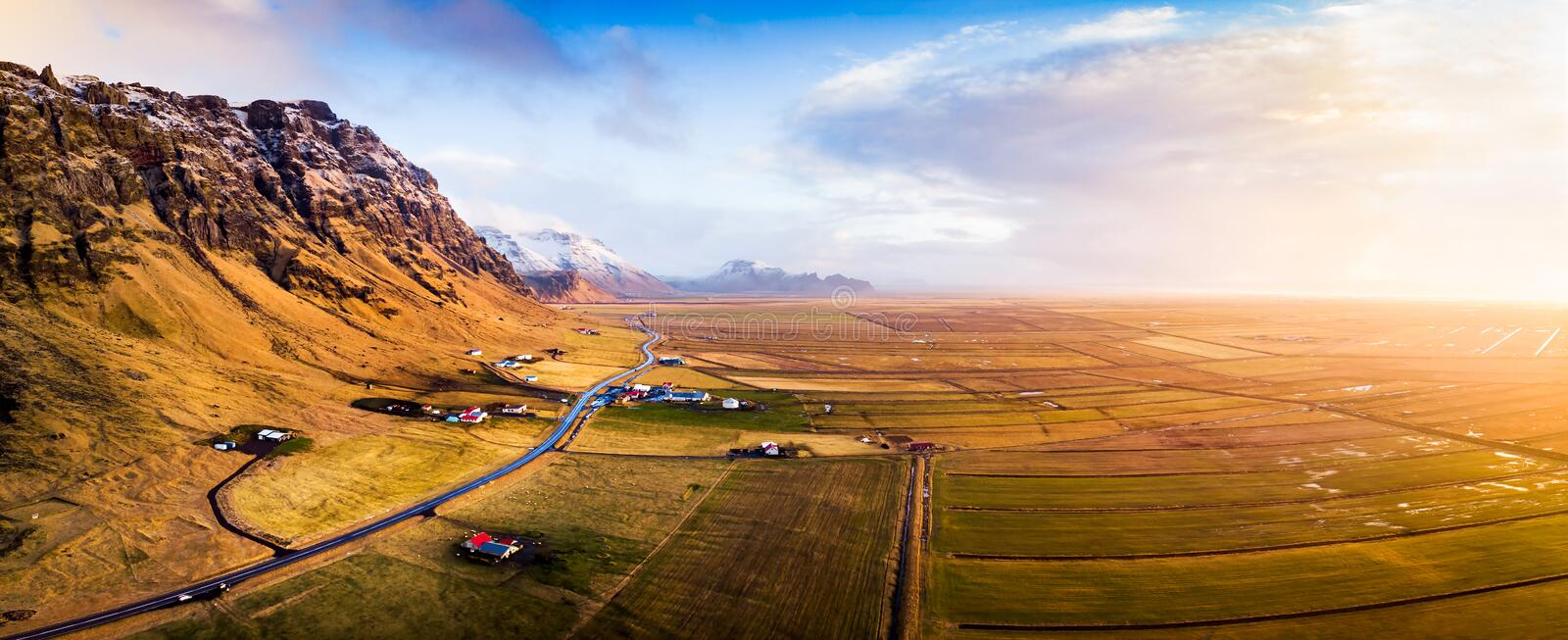 Village and scenic road in Iceland aerial panoramic view. At sunset stock image