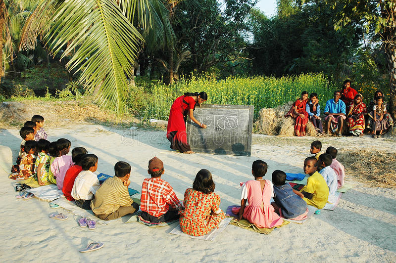 Village school. A young girl student on a gap year holds an adult & childs literacy class at the village of Sundarban-West Bengal. Literacy campaigns have stock image