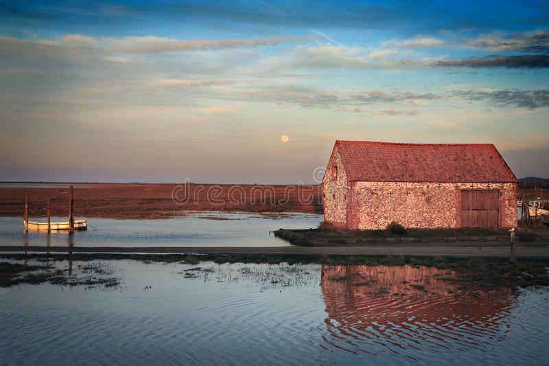 Sunset at Thornham Old Harbour. The village is separated from the sea by marshes and The  Coal Barn lit up by the late evening sun. Thornham old harbour in North royalty free stock photo