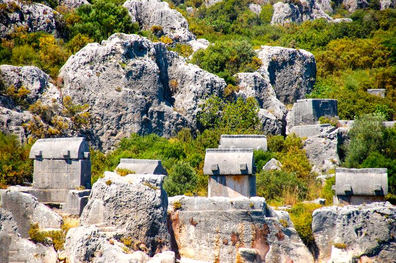 Lycian tombs in Simena. In the village of Simena, unique Lycian tombs carved into the rocks, as well as sarcophagi with covers in the form of inverted boats royalty free stock images
