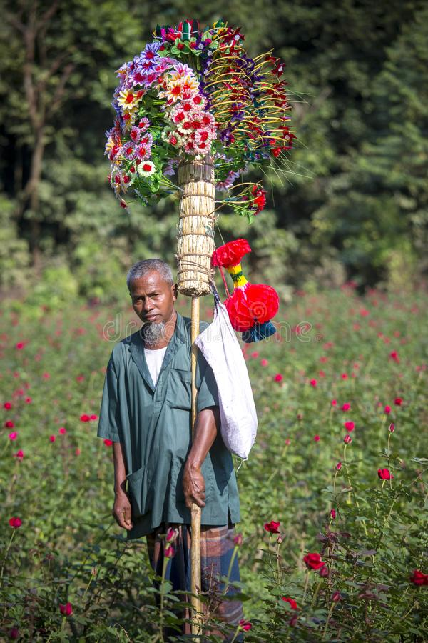 A village street hawker Kohinur age 68, selling colorful paper flowers, Dhaka, Bangladesh. A village street hawker deals in various things by hawking from royalty free stock image