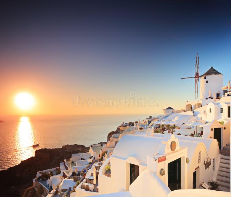 Village sur l'île de Santorini et un coucher du soleil photographie stock libre de droits