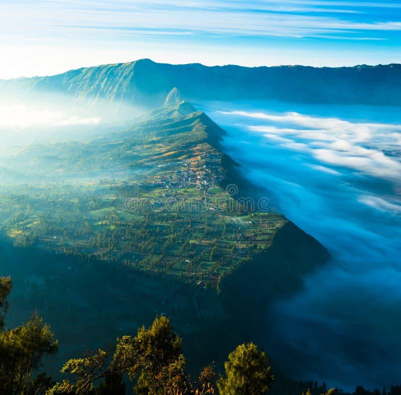 Village sur la montagne avec le brouillard pendant le lever de soleil photos stock