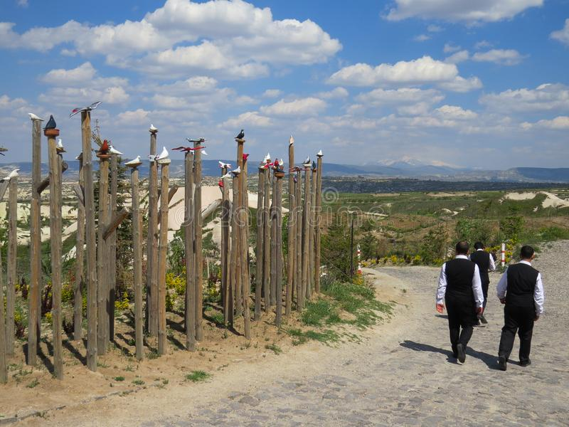 Village Uchisar. Sign of the Pigeon Valley. Three men in black suits and white shirts are walking along the road. Cappadocia, Turkey royalty free stock photography