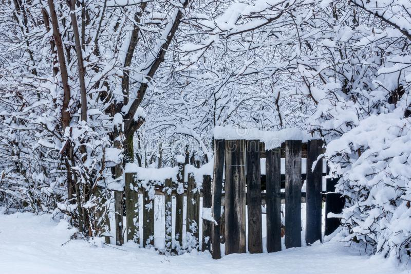 Village wooden fence covered with big snow on cold winter day royalty free stock photos