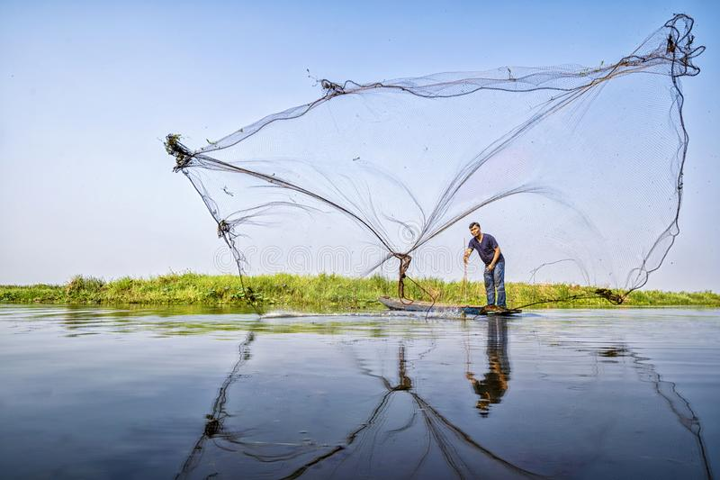 Villagers are casting fish. Fisherman Fishing Nets. Throwing fishing net during morning on a wooden boat, Thailand royalty free stock photos