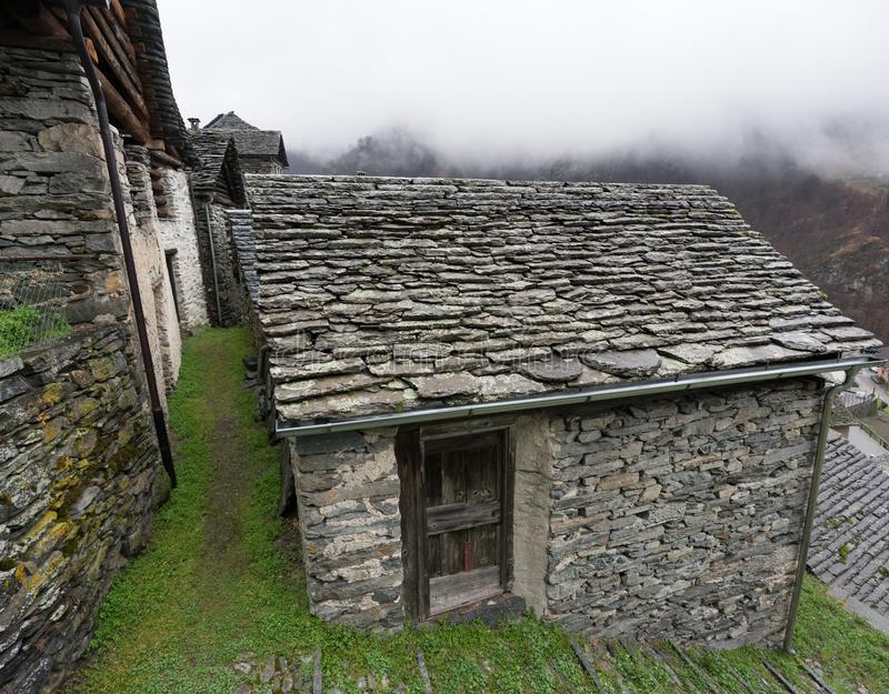 Villaggio alpino tradizionale con molte piccole case di legno e di pietra e un contesto della cascata della montagna immagine stock