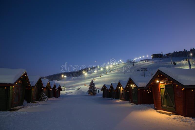 Villaggio del mercato di inverno in Levi, Finlandia nel evenig sul fondo della teleferica dello sci immagini stock