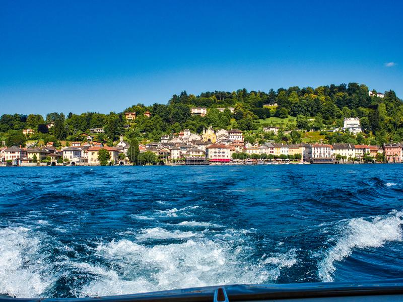 Villaggio di San Giulio visto dalla barca che si dirige all'isola di San Giulio Italy su un pomeriggio di estate fotografie stock