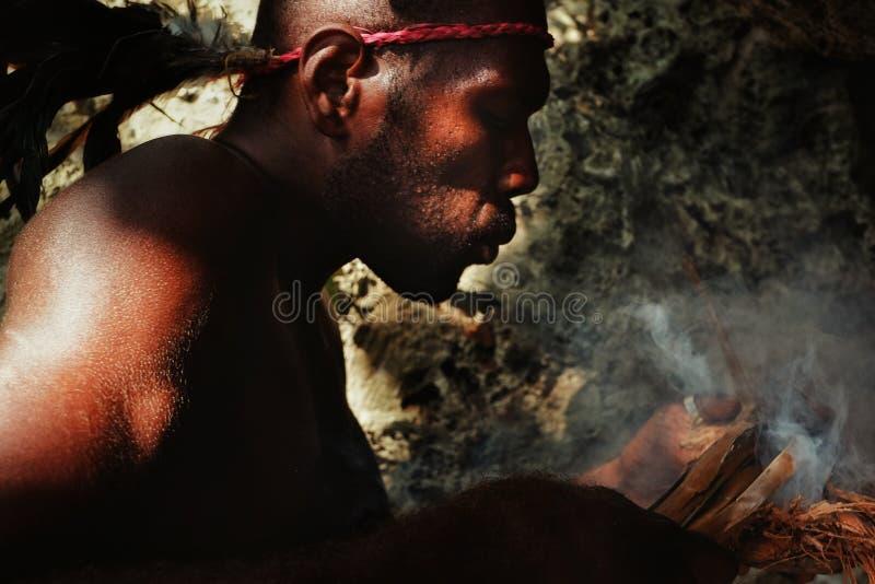 Villaggio di Walarano, isola di Malekula/Vanuatu - 9 LUGLIO 2016: uomo tribale locale che soffia ad un fuoco per accenderlo sul t immagini stock libere da diritti