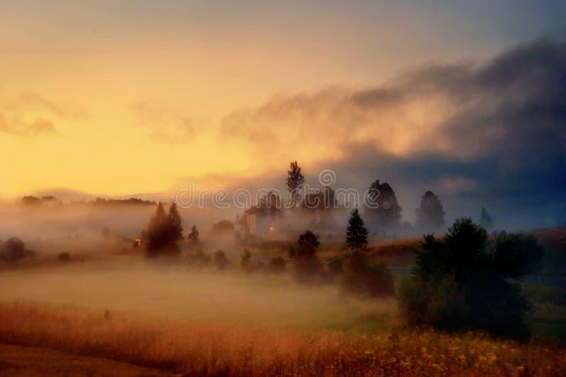 Villaggio nebbioso al crepuscolo fotografia stock