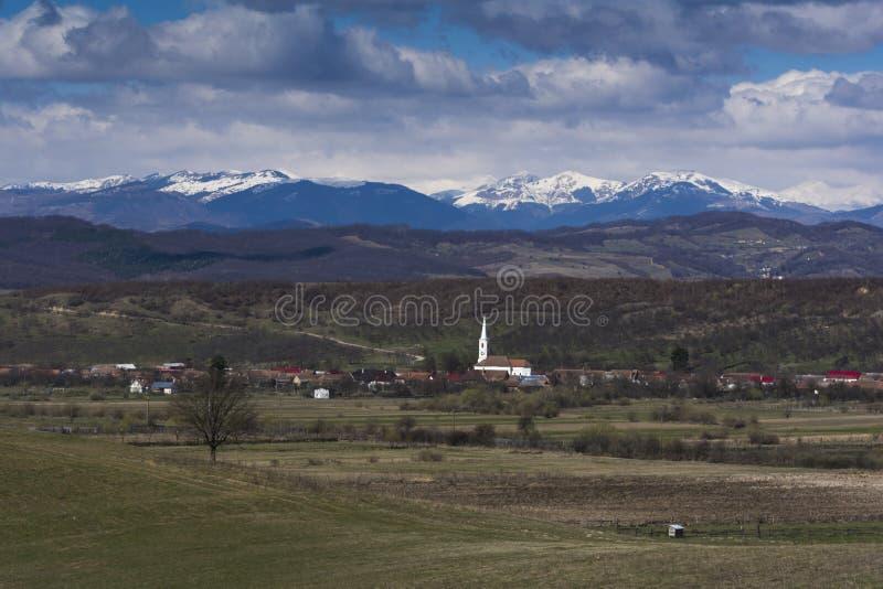 Villaggio rumeno con le montagne carpatiche nei precedenti coperti in neve fotografie stock