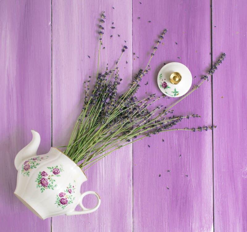 Villaggio rustico d'annata dei fiori viola del fondo di vista superiore del bollitore della teiera della lavanda immagini stock libere da diritti