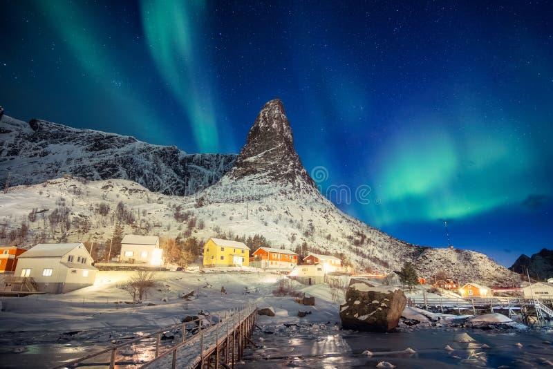 Villaggio scandinavo variopinto con l'aurora boreale sopra la montagna di punta a Lofoten fotografie stock libere da diritti