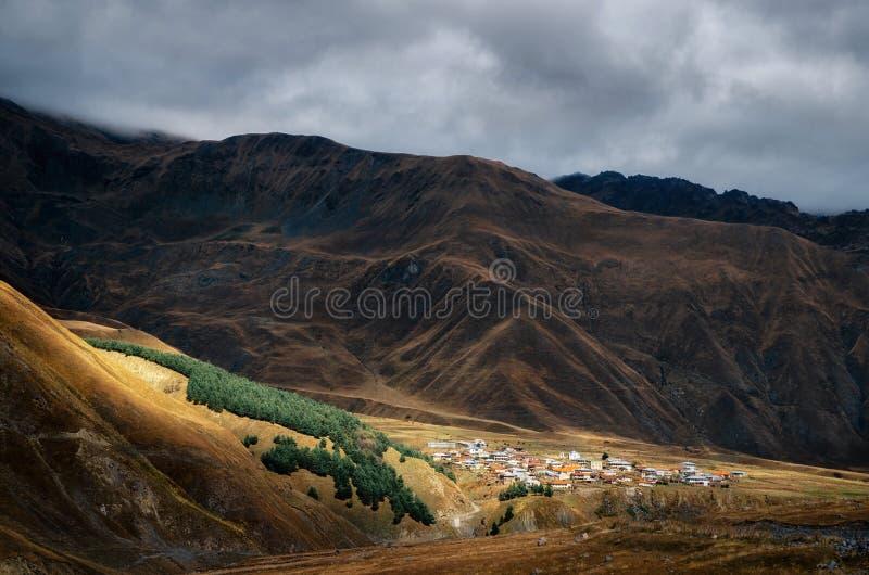 Villaggio sulla collina di maggiori montagne di Caucaso, Kazbegi, Georgia immagini stock libere da diritti