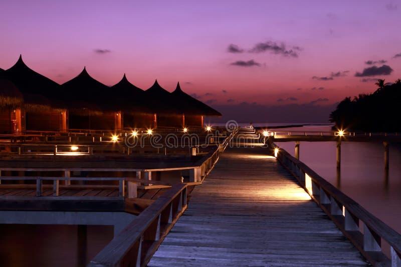 Villas Maldives de l'eau de coucher du soleil images libres de droits