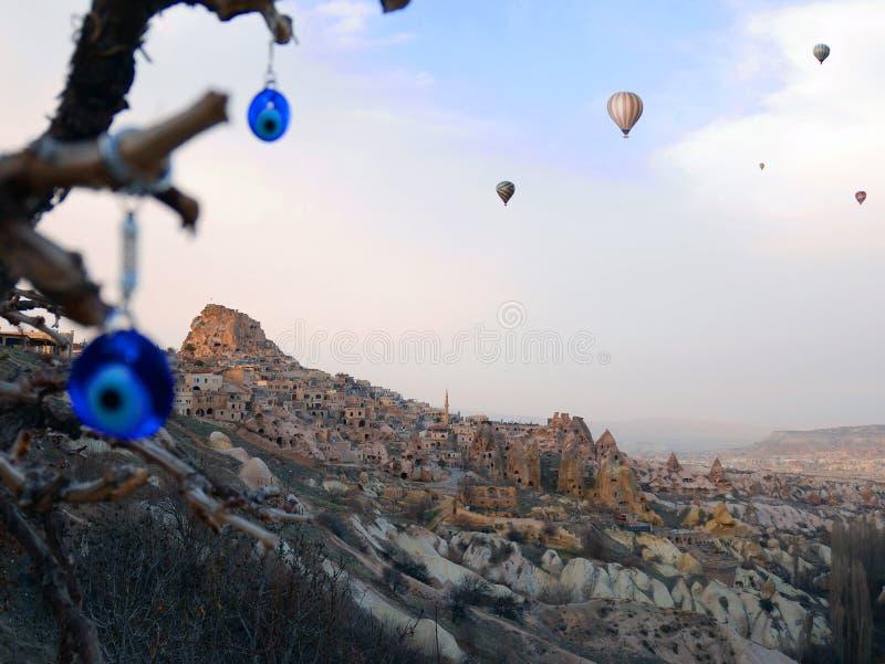 Ville antique Uchisar avec des charmes et des ballons d'oeil mauvais photos stock