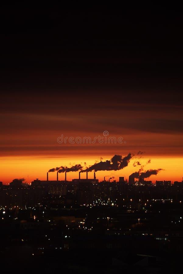 Ville au coucher du soleil Le contour des bâtiments et des cheminées de tabagisme photographie stock libre de droits