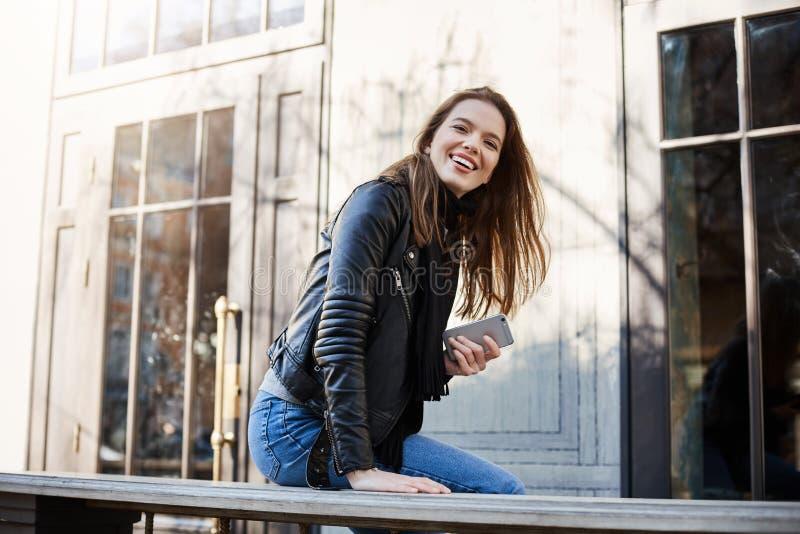 Ville avec les citoyens positifs Belle femme à la mode dans la veste en cuir se reposant près du café, se penchant sur le banc, r image stock