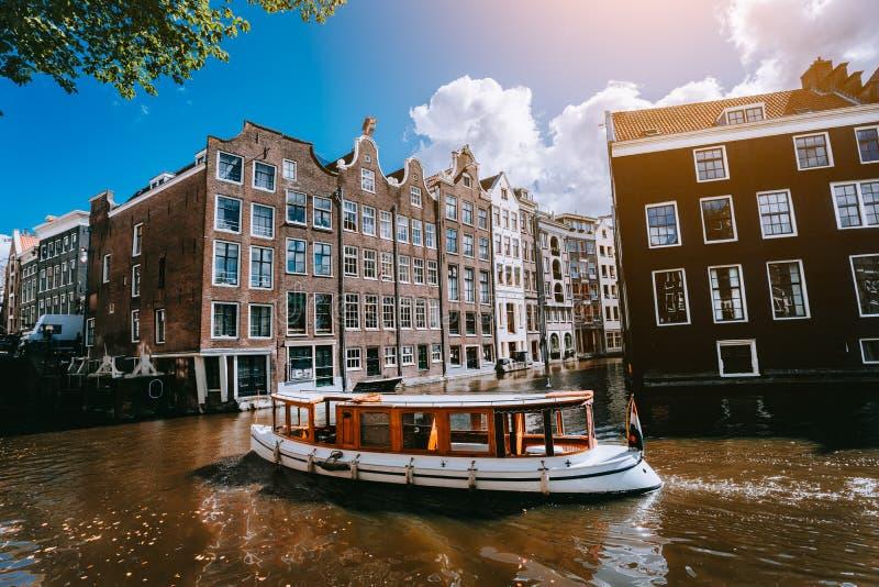 Ville d'Amsterdam dans le paysage pittoresque de la Hollande, bateaux blancs sur un canal entre les maisons historiques photos libres de droits