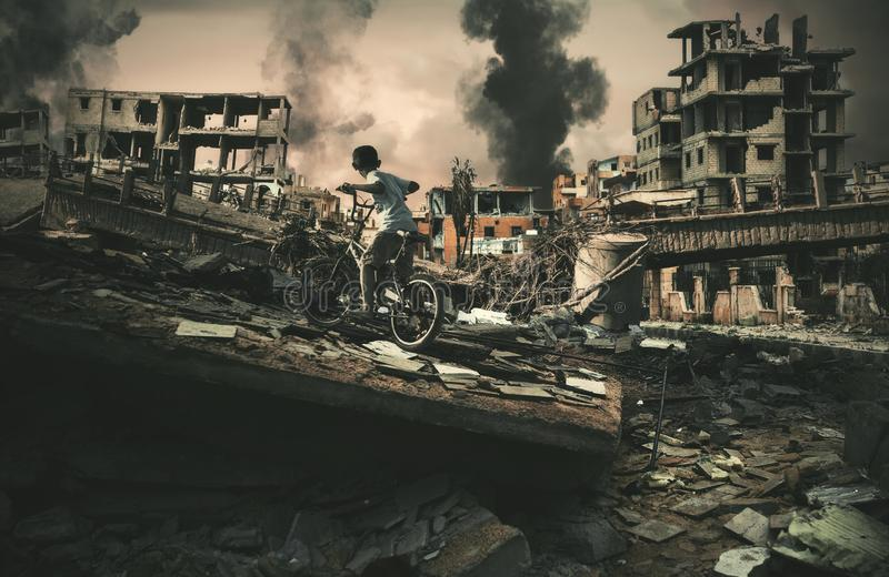 Ville dans la guerre et la bicyclette sans abri d'équitation de petit enfant photographie stock libre de droits