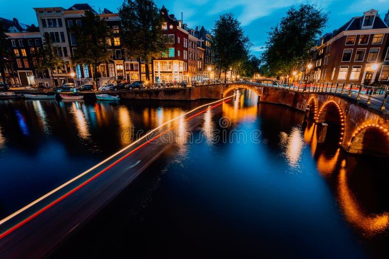 Ville de centre-ville lumineuse par soirée d'Amsterdam Réflexions touristiques de traînées et de pont de lumière de bateau chez l photographie stock libre de droits