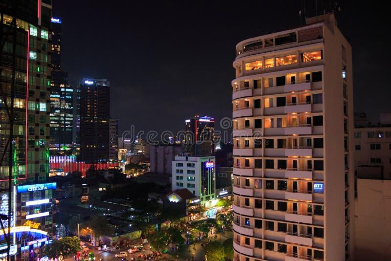 Ville de Ho Chi Minh, Vietnam - d?cembre 2018 : paysage urbain avec la rue de marche, le haut b?timent, l'enseigne au n?on et les photo stock
