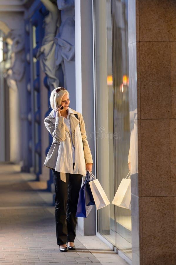 Ville de soirée de lèche-vitrines de jeune femme photo stock