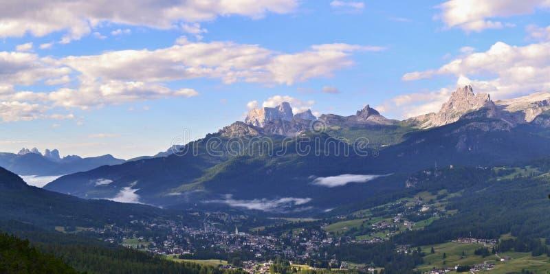 Ville et forêt en vallée sous des crêtes de haute montagne photo libre de droits