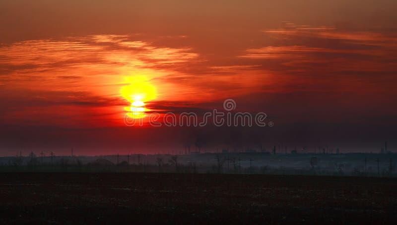 Ville industrielle dans la fumée sale sur le coucher du soleil photo stock