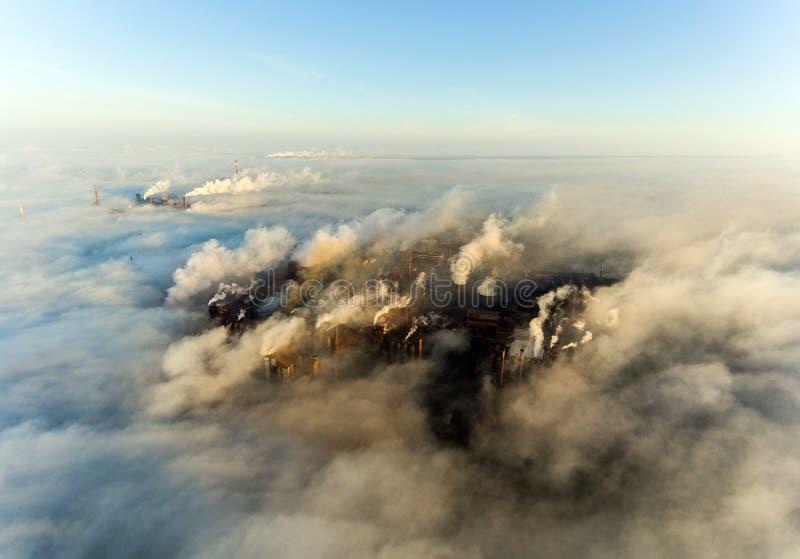 Ville industrielle de Mariupol, Ukraine, dans la fumée des ensembles industriels et du brouillard à l'aube photographie stock libre de droits