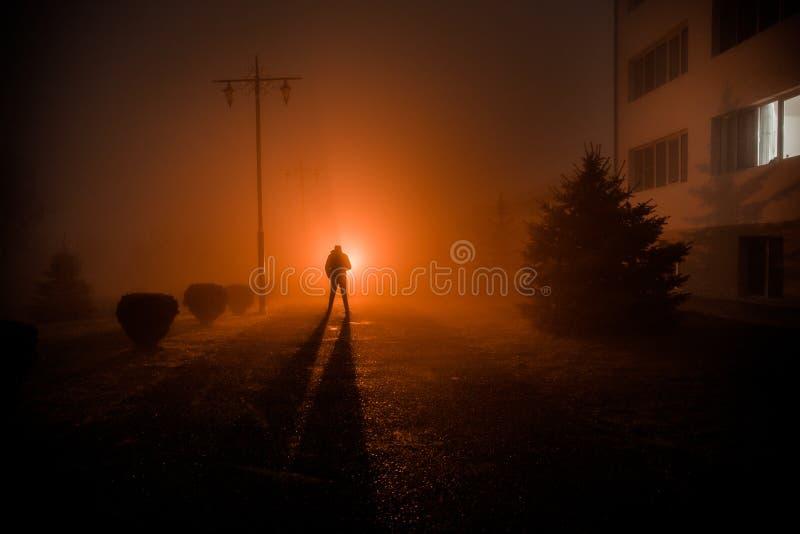 Ville la nuit en brouillard dense Lumières surréalistes de paysage mystique avec l'homme rampant La silhouette de l'homme de marc image libre de droits