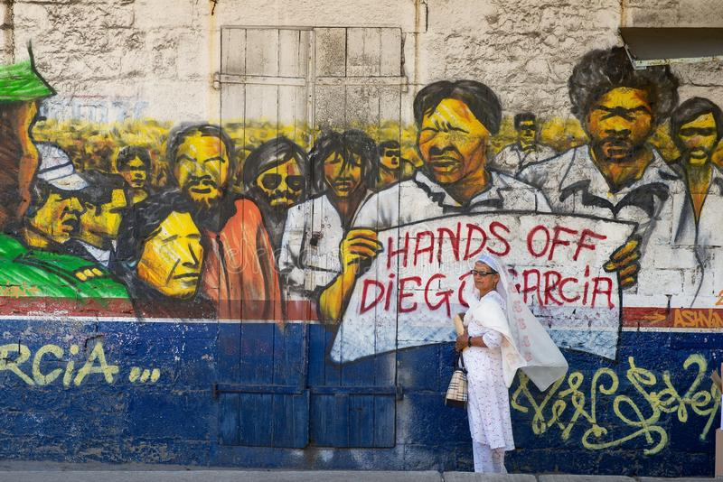 Woman stands at the street with political poster `Hands off Diego Garcia` painted at the wall in Ville Noire, Mauritius island. stock photo