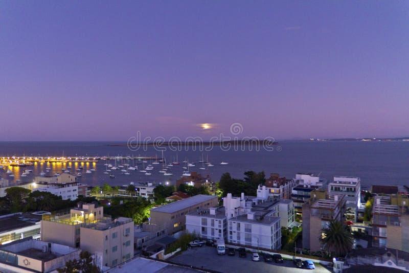Ville portuaire avec les bateaux, l'île et la lune Punta del Este images libres de droits