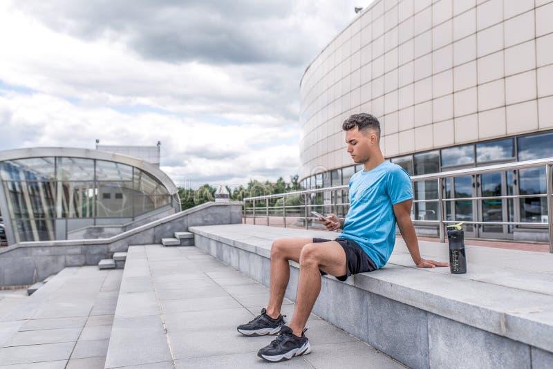 Ville sportive d'été d'homme, smartphone se reposant de mains d'étapes, Internet social d'application de réseaux de formation en  photo libre de droits